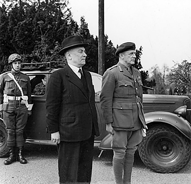 The Belgian Prime Minister Hubert Pierlot (middle) and Major General R. G. Sturges (right) stand to attention while the Royal Salute is played during Pierlot's visit to the Special Services at Group HQ on 21 April 1944. © IWM